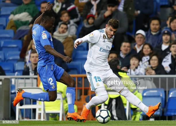 Theo Hernandez of Real Madrid competes for the ball with Dakonam Djene of Getafe during the La Liga match between Real Madrid and Getafe at Estadio...
