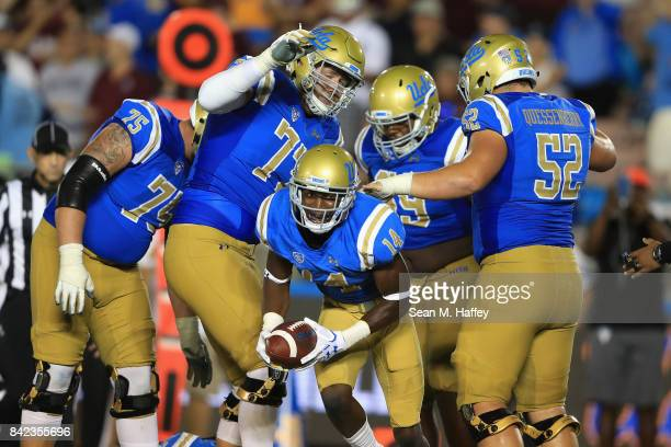 Theo Howard reacts after a touchdown on a pass play as Scott Quessenberry Kolton Miller and Andre James of the UCLA Bruins react during the second...