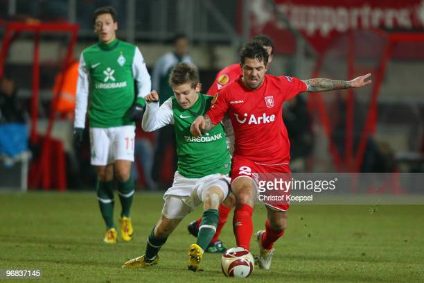 Theo Janssen of Enschede tackles Marko Marin of Bremen during the UEFA Europa League knockout round first leg match between FC Twente Enschede and SV...