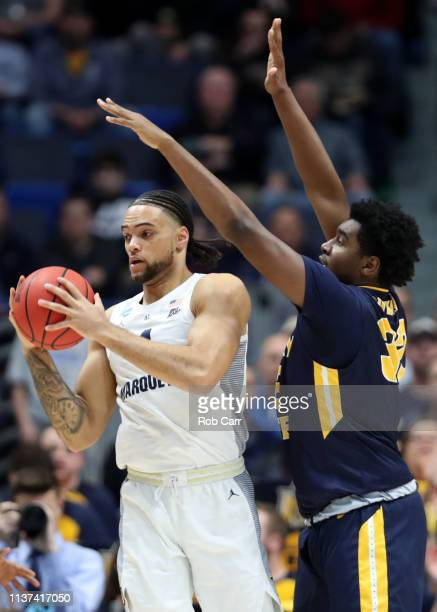 Theo John of the Marquette Golden Eagles is defended by Darnell Cowart of the Murray State Racers during the first round game of the 2019 NCAA Men's...