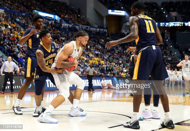 Theo John of the Marquette Golden Eagles is defended by Jaiveon Eaves of the Murray State Racers during the first round game of the 2019 NCAA Men's...