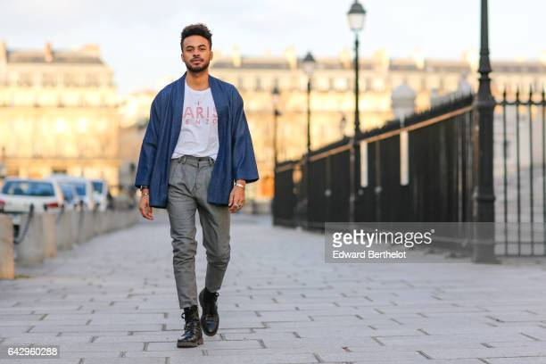 Theo Kimbaloula fashion blogger wears a Kenzo white tshirt a Carubas blue denim kimono and Zara gray pants on February 18 2017 in Paris France
