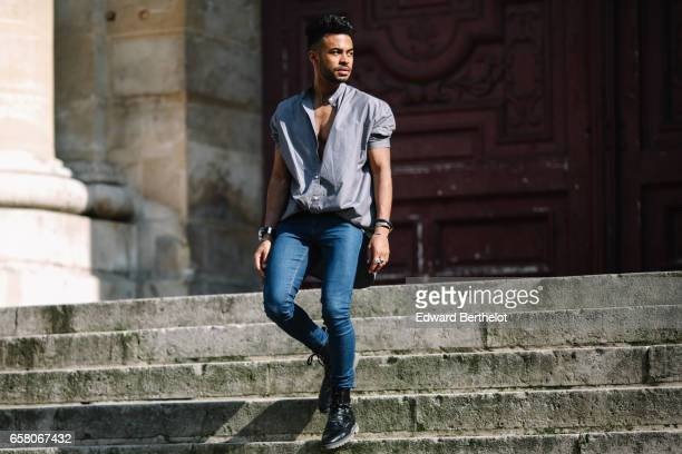 Theo Kimbaloula fashion blogger wears a MUJI shirt Asos blue denim jeans Asos black leather boots and a Diesel watch on March 26 2017 in Paris France