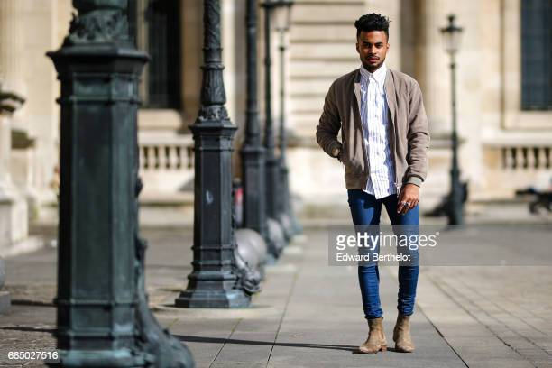 Theo Kimbaloula fashion blogger wears a Wac beige jacket a Wac shirt Asos blue jeans and The Kooples beige suede boots at the Louvre on April 2 2017...