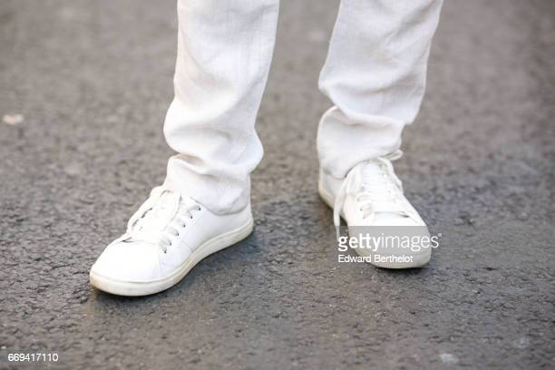 Theo Kimbaloula fashion blogger wears an Agnes B blue shirt Zara gray pants and Jules white shoes on April 9 2017 in Paris France