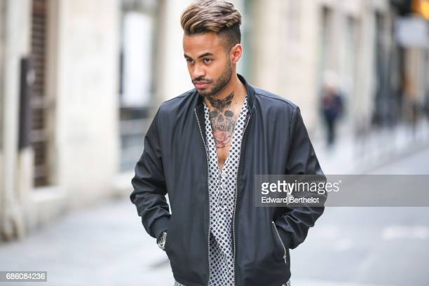 Theo Kimbaloula fashion blogger wears an Imperial tshirt with dots a WAC black bomber jacket blue denim jeans and white sneakers shoes on May 13 2017...