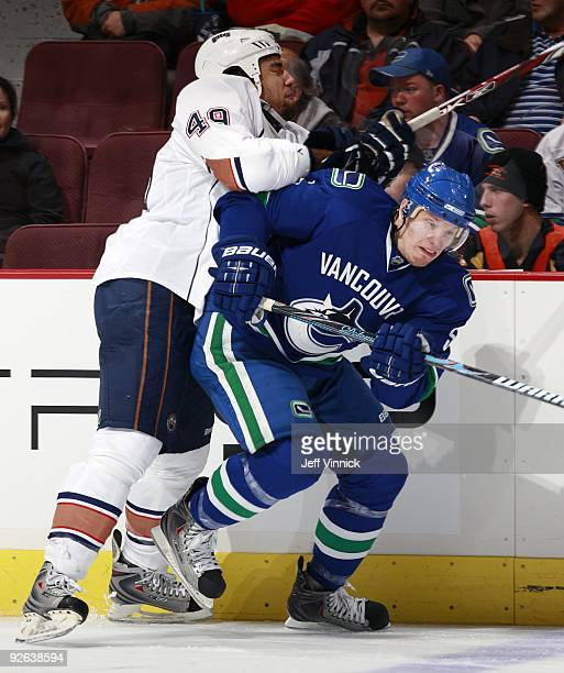 Theo Peckham of the Edmonton Oilers checks Christian Ehrhoff of the Vancouver Canucks during their game at General Motors Place on October 25 2009 in...