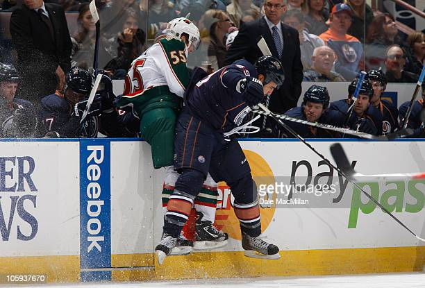 Theo Peckham of the Edmonton Oilers checks Nick Schultz of the Minnesota Wild in first-period action at Rexall Place October 21, 2010 in Edmonton,...