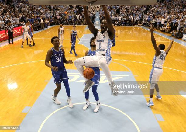 Theo Pinson of the North Carolina Tar Heels dunks the ball as teammates Wendell Carter Jr and Marvin Bagley III of the Duke Blue Devils watch on...