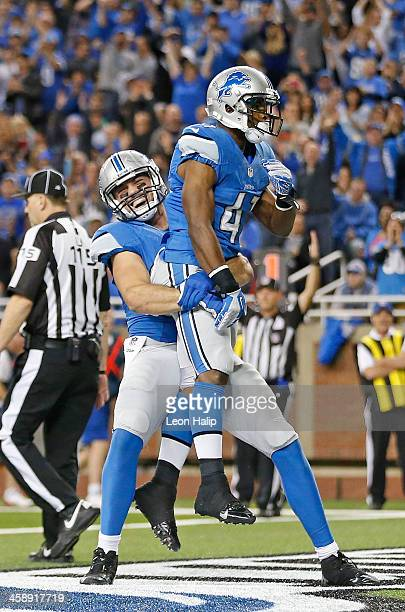 Theo Riddick of the Detroit Lions celebrates after scoring on a short run with teammate Joseph Fauria during the fourth quarter of the game againsts...