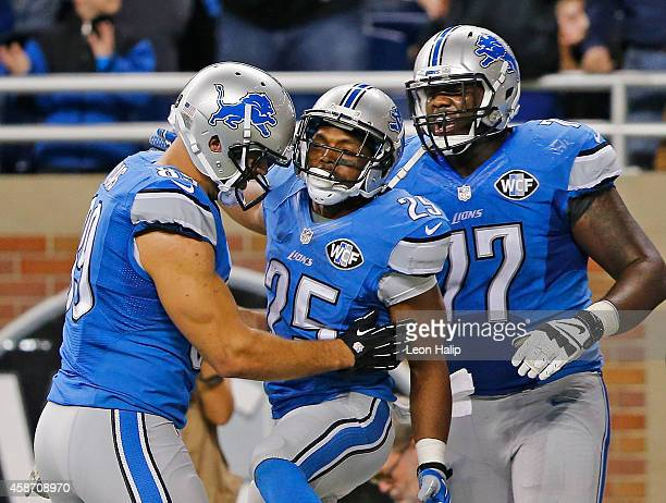 Theo Riddick of the Detroit Lions celebrates after scoring the game winning touchdown with teammates Kellen Davis and Cornelius Lucas of the Detroit...