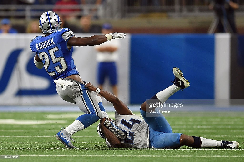 Theo Riddick #25 of the Detroit Lions is brought down by Daimion Stafford #24 of the Tennessee Titans during a game at Ford Field on September 18, 2016 in Detroit, Michigan.