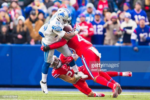 Theo Riddick of the Detroit Lions is brought down by Micah Hyde and Tremaine Edmunds of the Buffalo Bills during the fourth quarter at New Era Field...