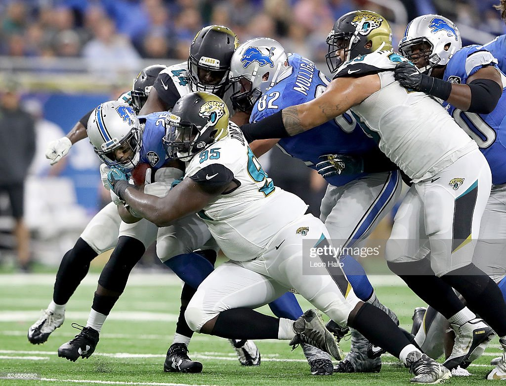 Theo Riddick #25 of the Detroit Lions is gang tackled by the Jacksonville Jaguars during fourth quarter at Ford Field on November 20, 2016 in Detroit, Michigan.