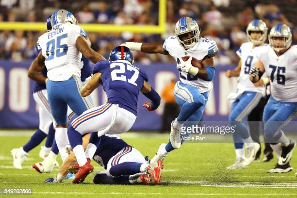 Theo Riddick of the Detroit Lions runs the ball against Darian Thompson of the New York Giants in the fourth quarter during their game at MetLife...