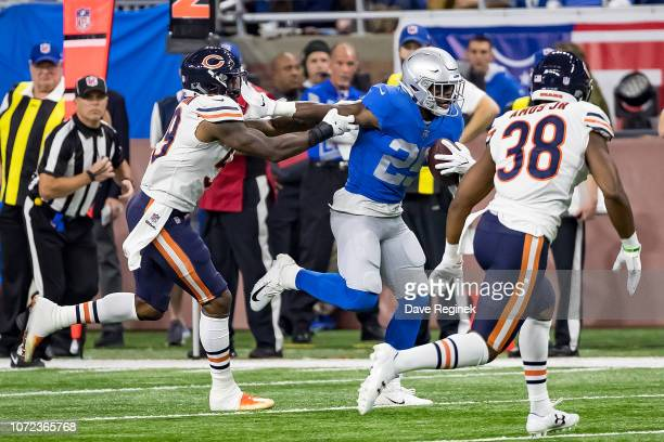 Theo Riddick of the Detroit Lions runs with the football and stiff arms Danny Trevathan of the Chicago Bears during an NFL Thanksgiving Day game at...
