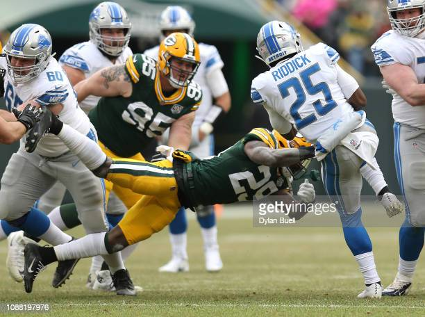 Theo Riddick of the Detroit Lions spins away from a diving Kentrell Brice of the Green Bay Packers during the first half of a game at Lambeau Field...