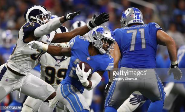 Theo Riddick of the Detroit Lions tries to avoid the grasp of Dante Fowler of the Los Angeles Rams during the second half at Ford Field on December 2...