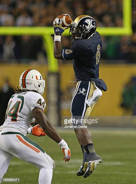 Theo Riddick of the Notre Dame Fighting Irish catches a pass in front of Eddie Johnson of the Miami Hurricanes at Soldier Field on October 6 2012 in...