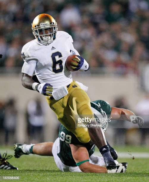 Theo Riddick of the Notre Dame Fighting Irish gets past the tackle of James Kittredge of the Michigan State Spartans during a fourth quarter run at...
