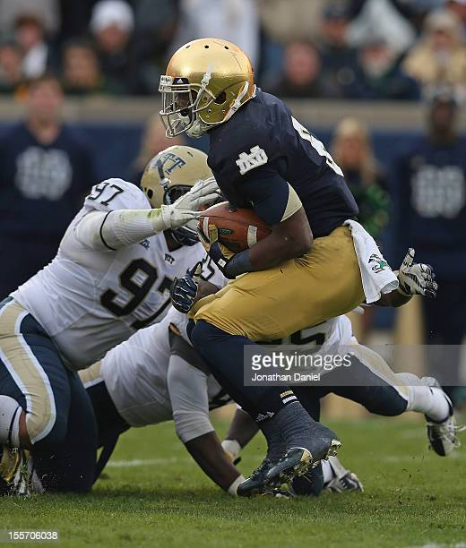 Theo Riddick of the Notre Dame Fighting Irish is dropped for a loss by Aaron Donald Joe Trebitz and Jason Hendricks of the Pittsburgh Panthers at...