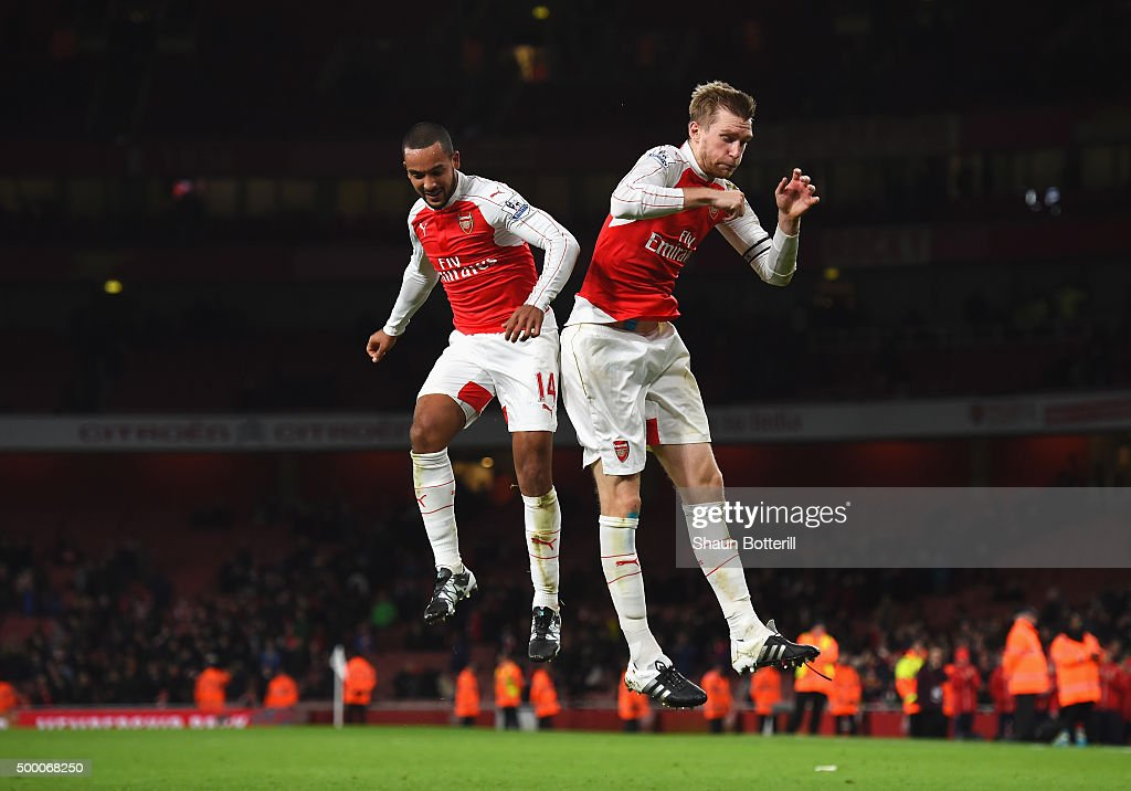 Theo Walcott (L) and Per Mertesacker (R) of Arsenal celebrate their team's 3-1 win in the Barclays Premier League match between Arsenal and Sunderland at Emirates Stadiumon December 5, 2015 in London, England.