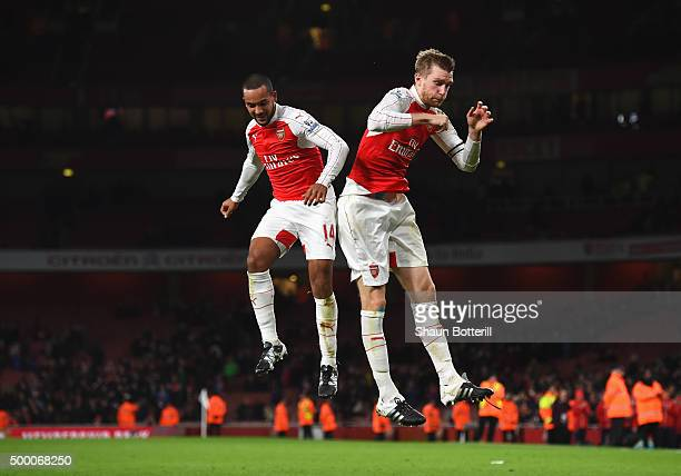 Theo Walcott and Per Mertesacker of Arsenal celebrate their team's 3-1 win in the Barclays Premier League match between Arsenal and Sunderland at...