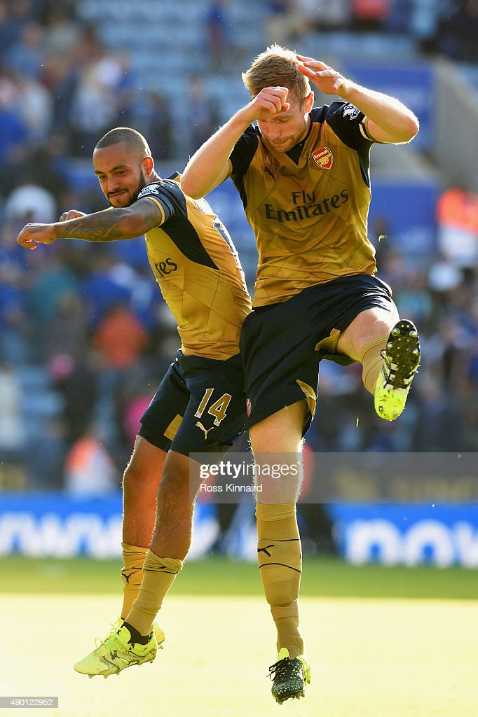 Theo Walcott (L) and Per Mertesacker (R) of Arsenal celebrate their team's 5-2 win in the Barclays Premier League match between Leicester City and Arsenal at The King Power Stadium on September 26, 2015 in Leicester, United Kingdom.