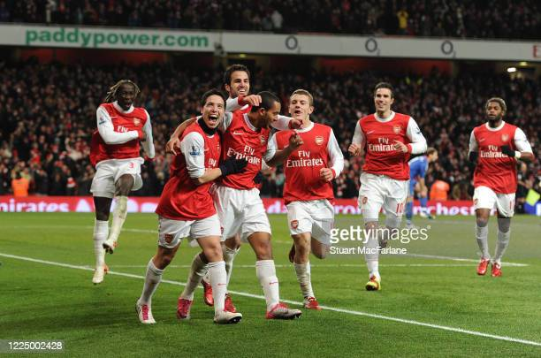 Theo Walcott celebrates scoring a goal for Arsenal with Samir Nasri and Cesc Fabregas during the Premier League match between Arsenal and Chelsea on...
