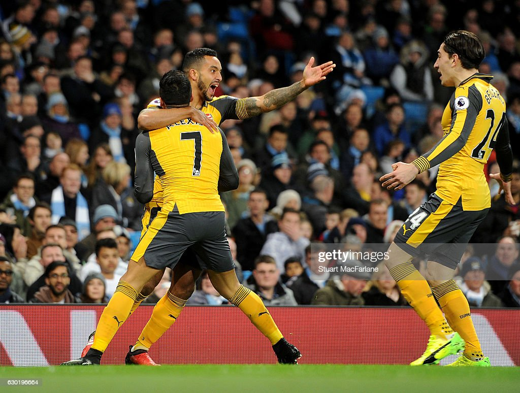 Theo Walcott celebrates scoring for Arsenal with (L) Alexis Sanchez amd (L) Hector Bellerin during the Premier League match between Manchester City and Arsenal at Etihad Stadium on December 18, 2016 in Manchester, England.