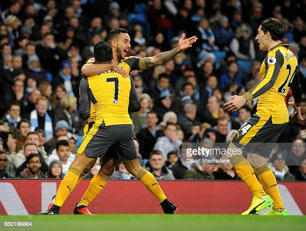 Theo Walcott celebrates scoring for Arsenal with Alexis Sanchez amd Hector Bellerin during the Premier League match between Manchester City and...