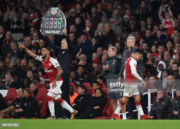 Theo Walcott comes on as a sub for Alexis Sanchez of Arsenal as Arsene Wenger the Arsenal Manager look on during the Premier League match between...