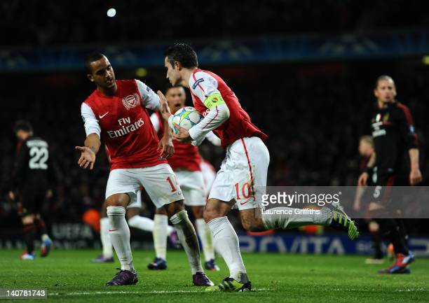 Theo Walcott congratulates Robin van Persie of Arsenal after he scored their third goal from the penalty spot during the UEFA Champions League Round...