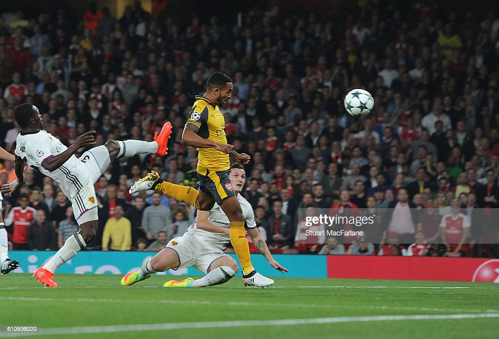 Theo Walcott heads past Basel defender Adama Traore to score for Arsenal during the UEFA Champions League match between Arsenal FC and FC Basel 1893 at Emirates Stadium on September 28, 2016 in London, England.