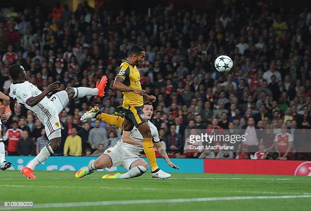 Theo Walcott heads past Basel defender Adama Traore to score for Arsenal during the UEFA Champions League match between Arsenal FC and FC Basel 1893...