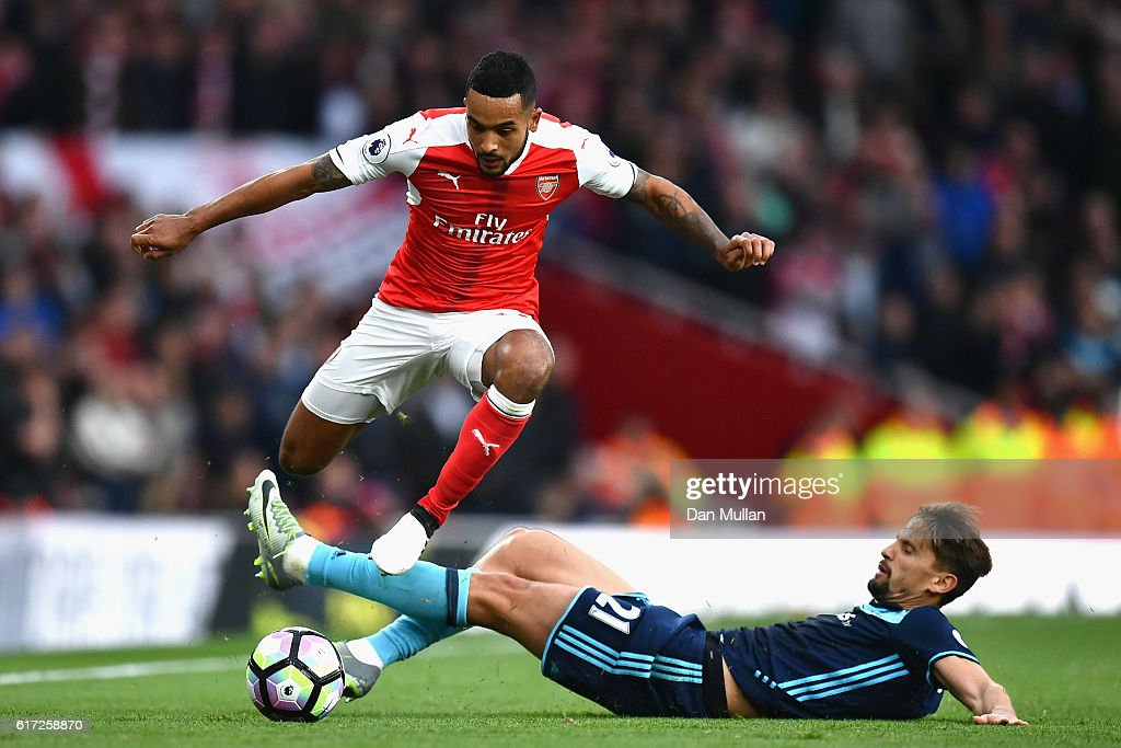 Theo Walcott of Arsenal and Gaston Ramirez of Middlesbrough compete for the ball during the Premier League match between Arsenal and Middlesbrough at Emirates Stadium on October 22, 2016 in London, England.