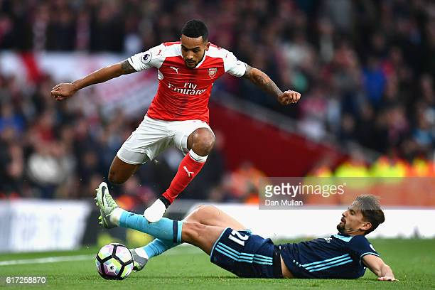 Theo Walcott of Arsenal and Gaston Ramirez of Middlesbrough compete for the ball during the Premier League match between Arsenal and Middlesbrough at...
