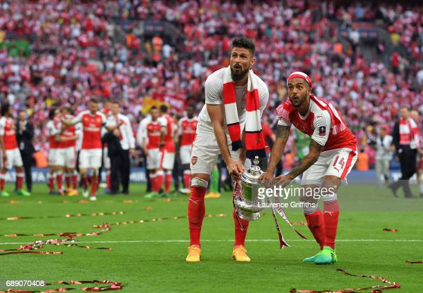 Theo Walcott of Arsenal and Olivier Giroud celebrate victory with the trophy following The Emirates FA Cup Final between Arsenal and Chelsea at...