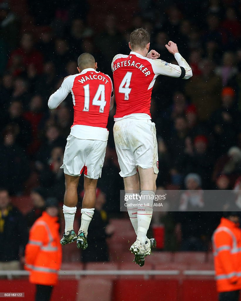 Theo Walcott of Arsenal and Per Mertesacker of Arsenal after the Barclays Premier League match between Arsenal and Newcastle United at Emirates Stadium on January 2, 2016 in London, England.