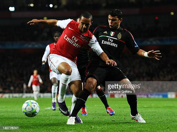 Theo Walcott of Arsenal and Thiago Silva of AC Milan battle for the ball during the UEFA Champions League Round of 16 second leg match between...