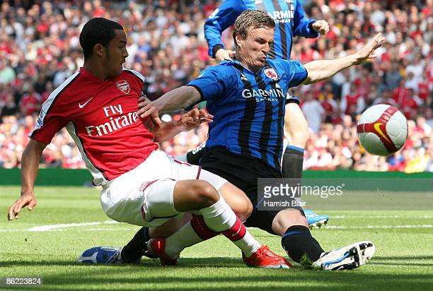 Theo Walcott of Arsenal battles for the ball with Robert Huth of Middlesbrough during the Barclays Premier League match between Arsenal and...