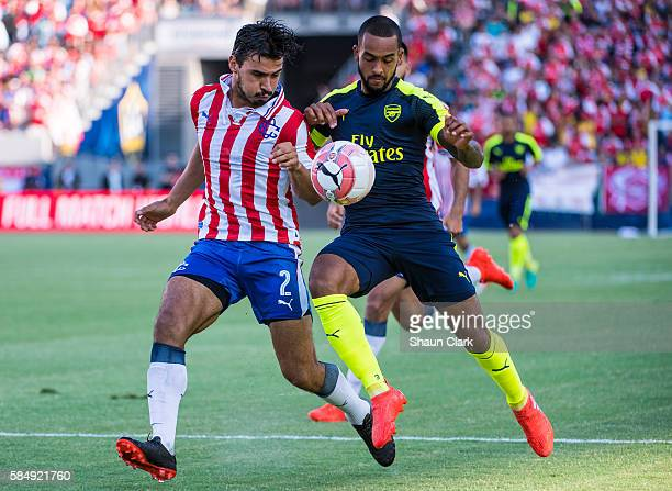 Theo Walcott of Arsenal battles Oswaldo Alanis of Guadalajara during the friendly match between Arsenal and CD Guadalajara at StubHub Center on July...