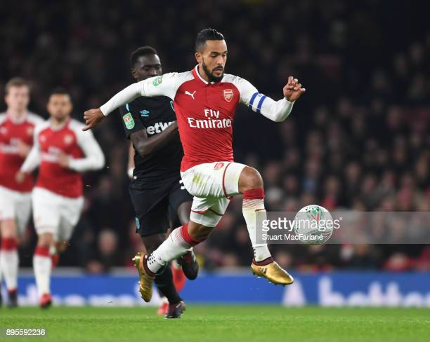 Theo Walcott of Arsenal breaks past Domingos Quina of West Ham during the Carabao Cup Quarter Final match between Arsenal and West Ham United at...