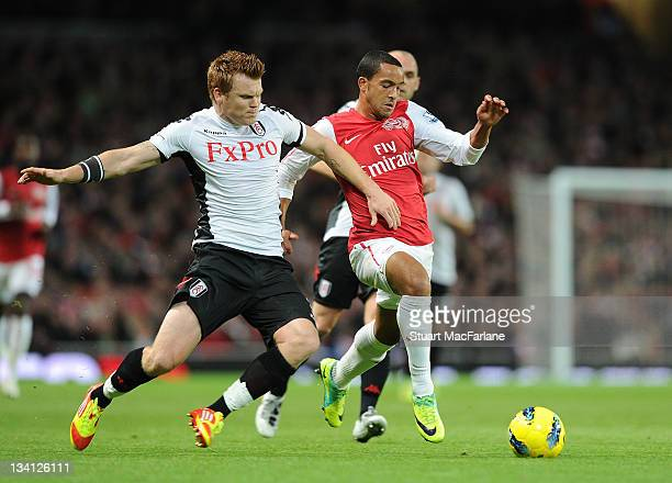 Theo Walcott of Arsenal breaks past John Arne Riise of Fulham during the Barclays Premier League match between Arsenal and Fulham at Emirates Stadium...