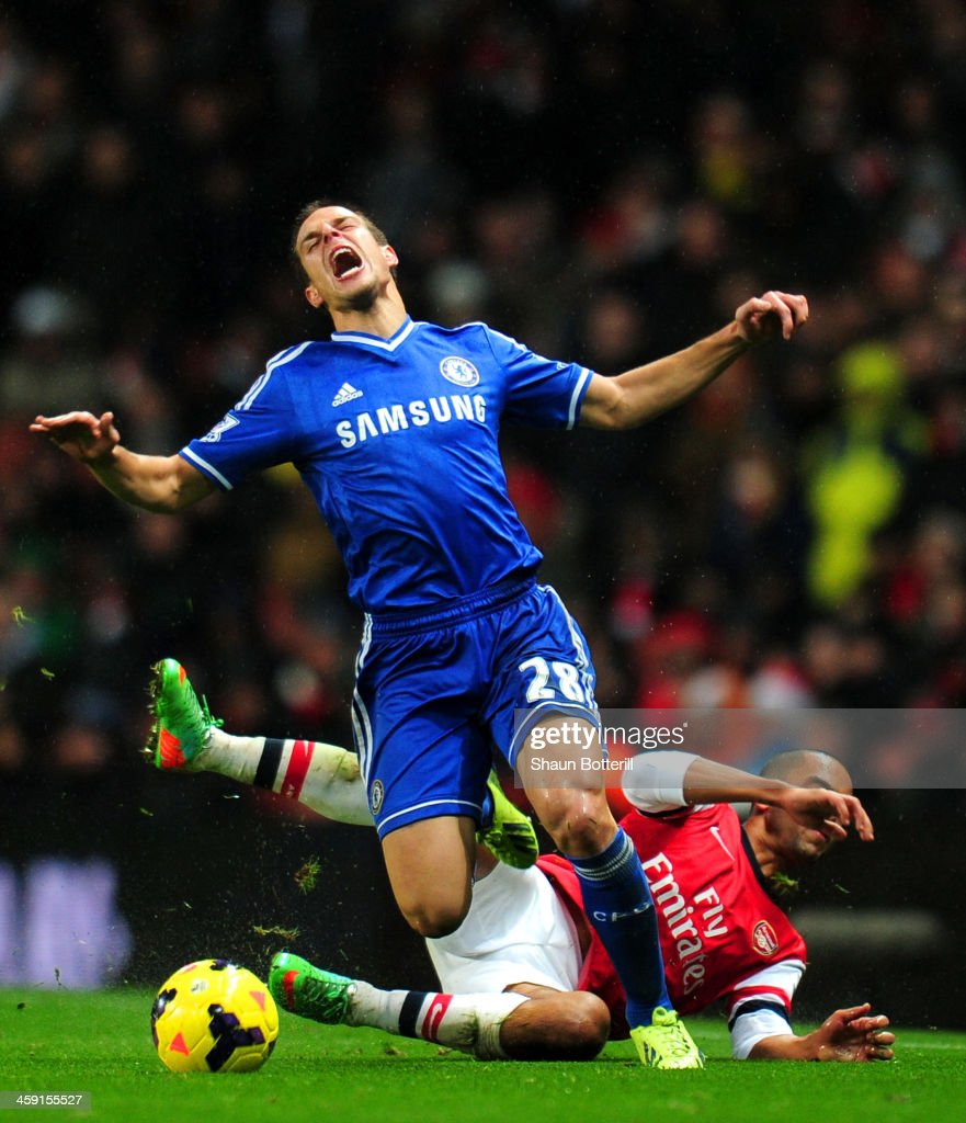 Theo Walcott of Arsenal brings down Cesar Azpilicueta of Chelsea during the Barclays Premier League match between Arsenal and Chelsea at Emirates Stadium on December 23, 2013 in London, England.
