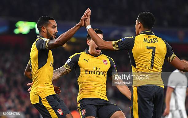 Theo Walcott of Arsenal ceclebrates with teammates Alexis Sanchez and Hector Bellerin after scoring the opening goal during the UEFA Champions League...
