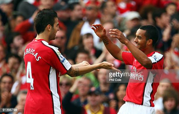 Theo Walcott of Arsenal celebrates after he scores his teams fifth goal with team mate Cesc Fabregas during the Barclays Premier League match between...