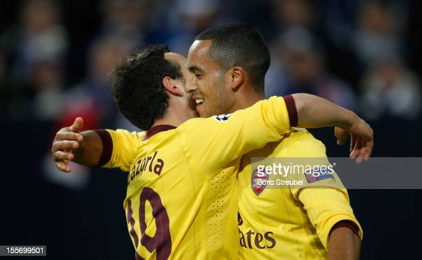 Theo Walcott of Arsenal celebrates after scoring his team's first goal with his team mate Santi Cazorla during the UEFA Champions League group B...