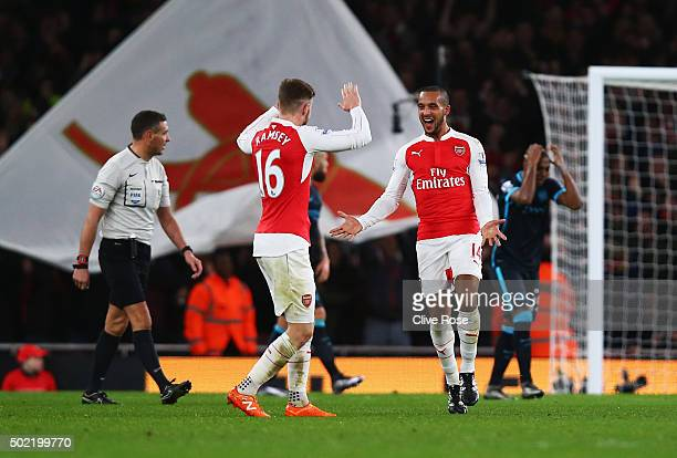 Theo Walcott of Arsenal celebrates scoring his team's first goal with Aaron Ramsey of Arsenal during the Barclays Premier League match between...