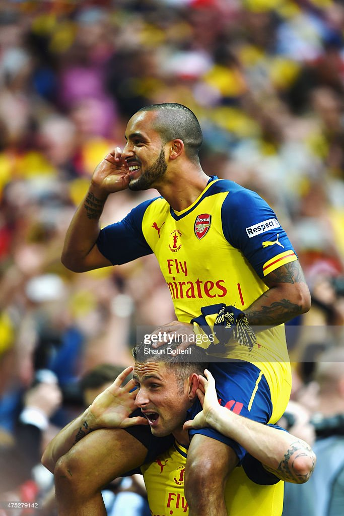 Theo Walcott of Arsenal celebrates victory on the shoulders of Olivier Giroud after the FA Cup Final between Aston Villa and Arsenal at Wembley Stadium on May 30, 2015 in London, England. Arsenal beat Aston Villa 4-0.